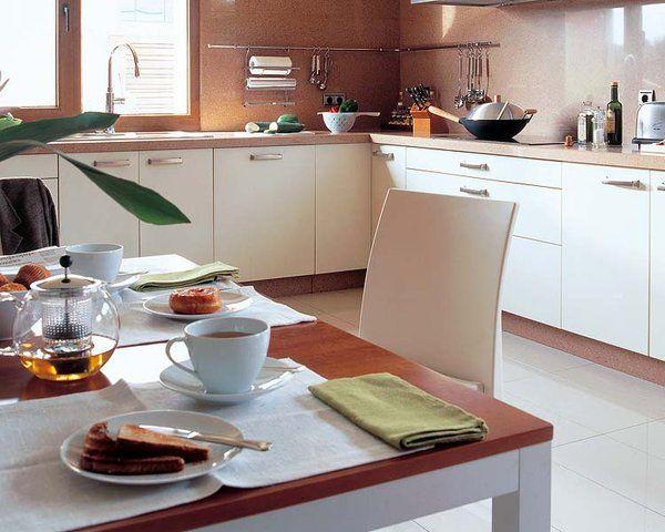 La acertada utilización de tonos suaves, aderezada con madera de cerezo y una cuidada iluminación, ha dado como resultado una cocina sencilla y cálida.