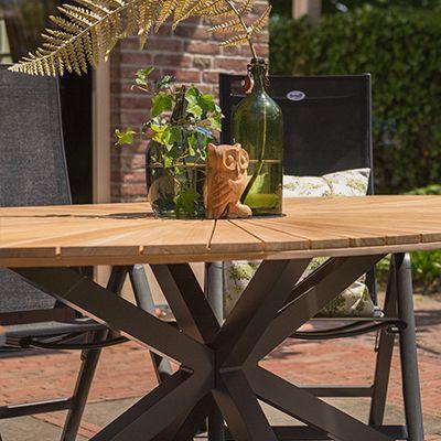 Teak in de mix! Uniek en vernieuwend! De ovale vorm van dit teak tafelblad maakt het blad speciaal. Ook het onderstel in de vorm van een kruis is uniek fascinerend!