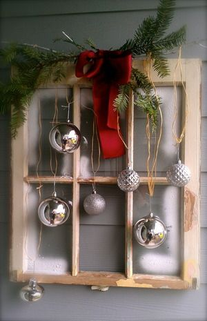 Christmas window idea with window pane, red bow, silver ornaments.