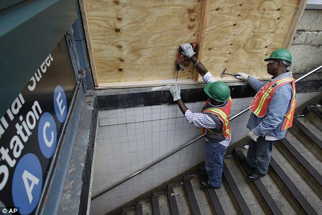 Preparations: Metropolitan Transportation Authority workers cover an entrance to the Canal St. A, C, and E station with plywood to help prevent flooding. October 28, 2012 - Hurricane Sandy