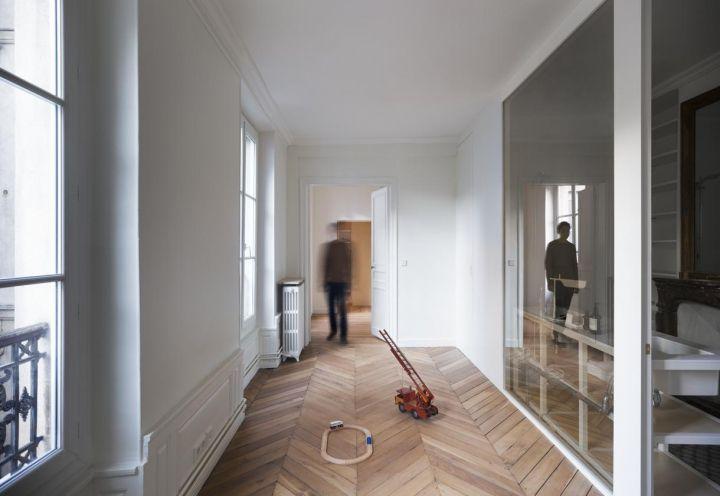 Uno specchio a due facce nell'appartamento parigino ristrutturato da CUT Architectures nasconde la stanza da bagno, posta di fronte ad un ampio corridoio, adibito a sala giochi per i piccoli di casa