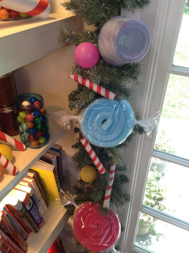 Holiday garland using deli containers (gum drops) pool noodles (candy) and pvc pipe (candy canes)