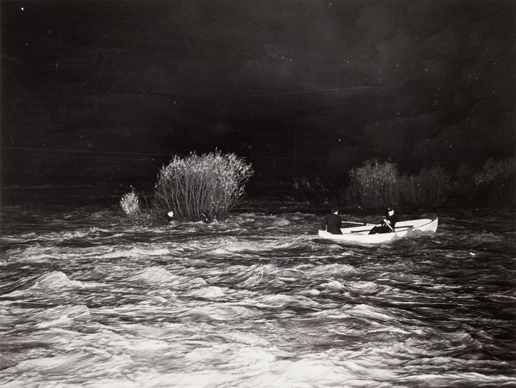 Lifesavers strain on oars to bring boat close enough to get lifeline to Jack Bates during six hour rescue in churning waters of the Don River after Hurricane Hazel, 1954.