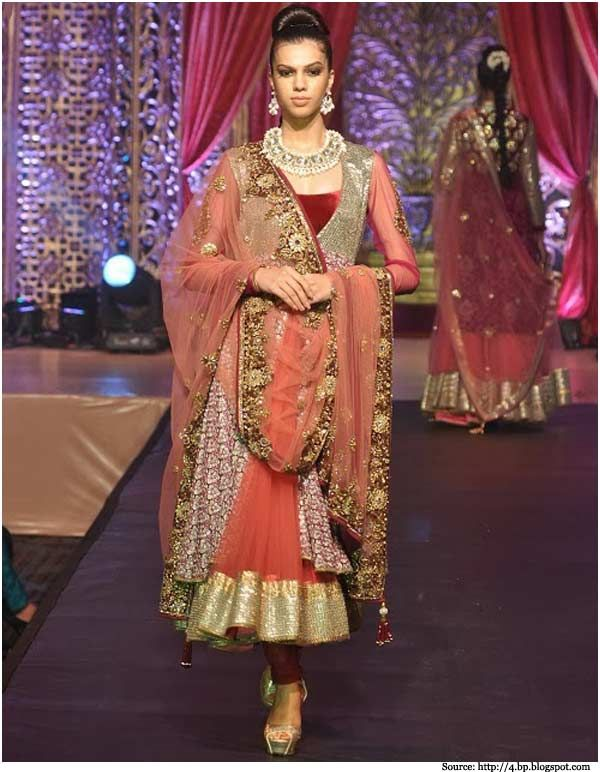 The fusion of the western and Indian style is not very new for this designer. In the above image, one can see the perfect combination of silver embroidery on a maroon fabric. The single shoulder suit is matched with a heavily embroidered dupatta and maroon chudidar.