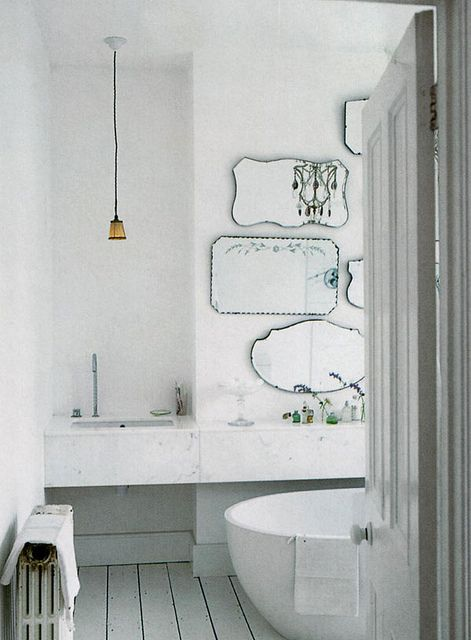 LOVE the all white bath; really intrigued by the mix of modern fixtures and vintage mirrors.  Unexpected.