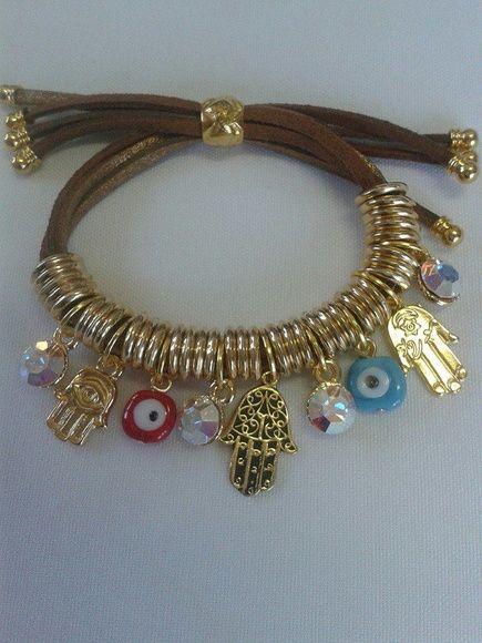 Bracelete com Simbolos de protecao,confeccionado com entremeios dourado, hamsa,olho grego e strass fruta cor. Cordao de camurca marrom. Fecho regualvel
