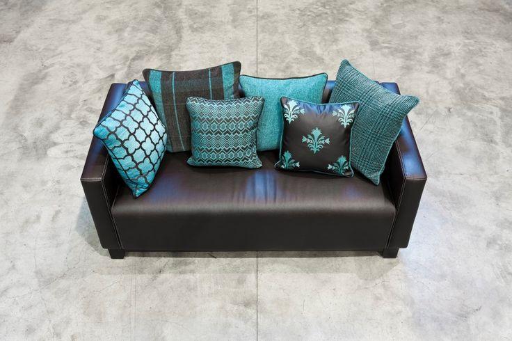 Eine einfache schwarze Couch aufpeppen? Kein Problem mit ein paar türkisen Farbakzenten von FINE.