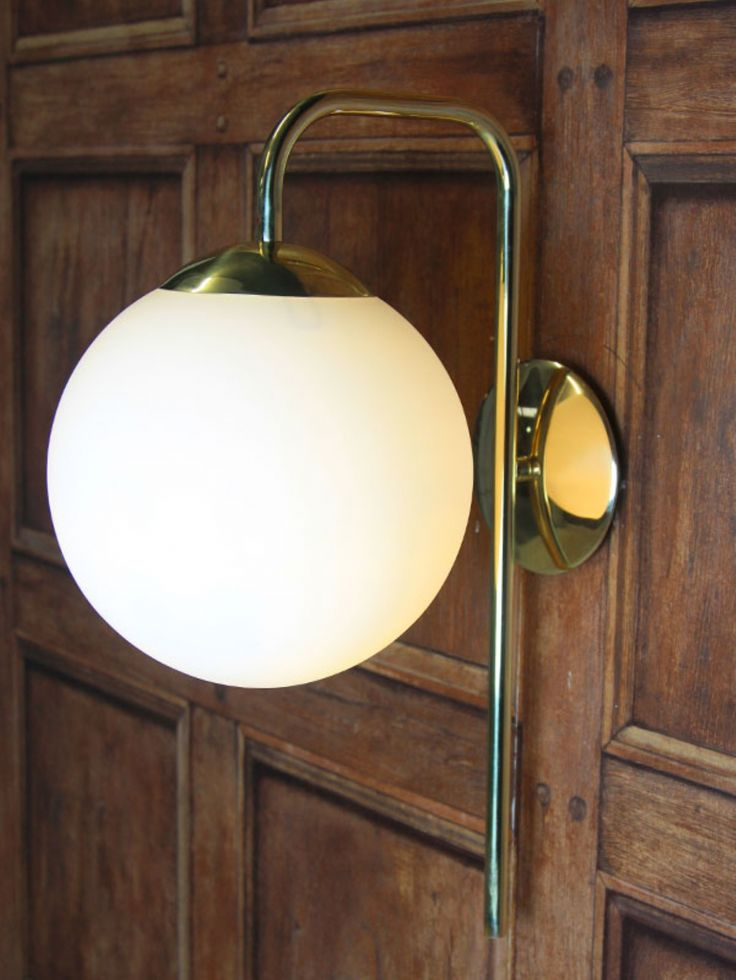 Polished brass wall light with opal glass globe