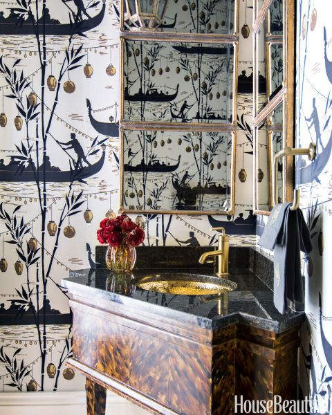 In a powder room, Cole & Son's Gondola wallpaper is a whimsical nod to Louisiana's small wood boats called pirogues. The sink, faucet, and towel ring are all by Kohler. Mirrors, Wisteria.