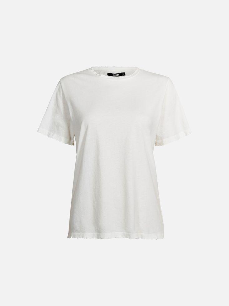 T-skjorte i børstet bomull med slitte kanter ved halsåpning, ermet og nederkant. Løstsittende passform.   Offwhite