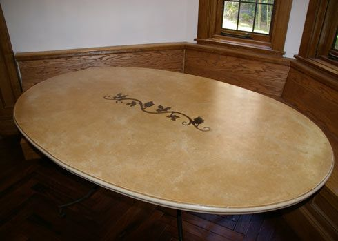 Oval Table With A Custom Iron Scroll Inlay In The Concrete Table Top.