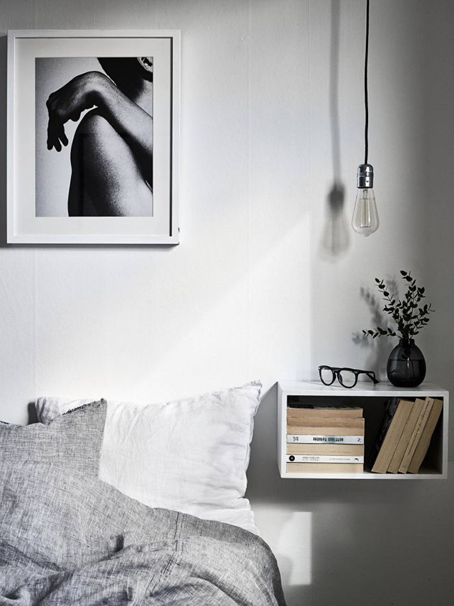 Minimalist moody bedroom with a floating IKEA shelf, gay linen bedding, and a single bulb pendant light