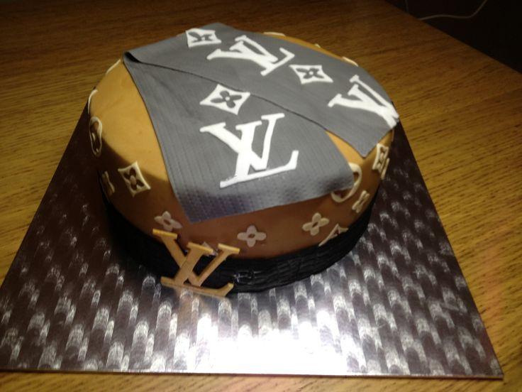 Gâteau Louis Vuitton Gâteau d'anniversaire de luxe pour un jeune homme de goût. Il s'agit ici d'une génoise chocolat agrémentée d'une mousse aérienne à souhait à la fraise. L'écharpe, la ceinture et sa boucle ainsi que tous les logos et symboles sont...