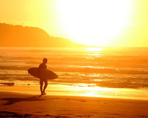 Surfer at sunset, Raglan, New Zealand
