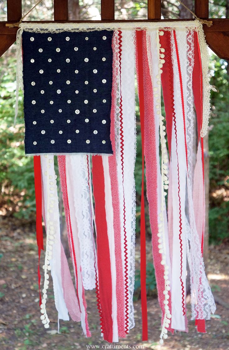 Shabby American flag created with scraps of fabric, lace, ribbon, ricrac and pompom fringe.