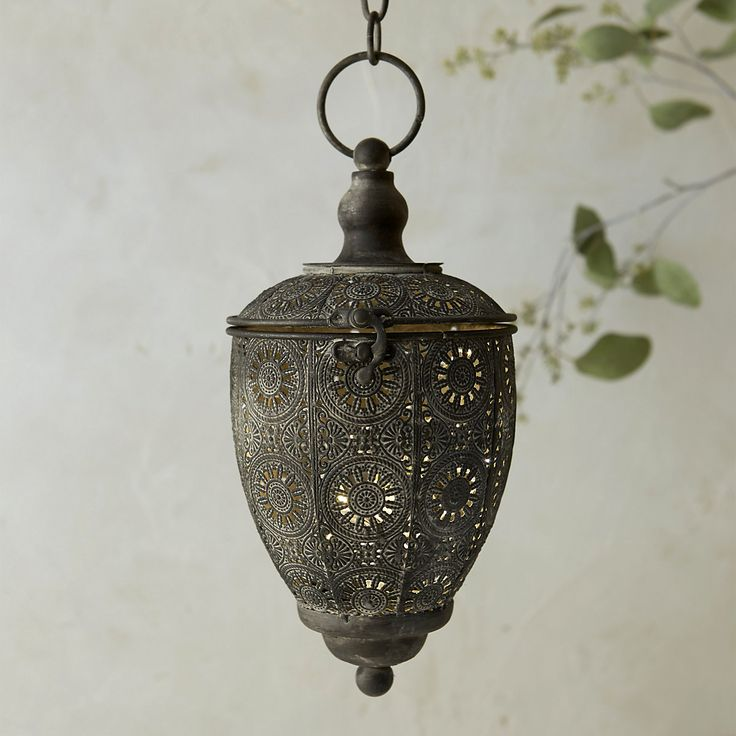 """A charming accent around the house, this antiqued lantern is hand-crafted from durable iron with a glass votive hurricane inside.- Iron, antiqued finish- Indoor use recommended - Hanging chain: 11""""- Imported10.25""""H, 5.3""""W, 5.7""""L"""