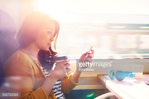 Stock Photo : Woman on a commuter train looking at her phone.