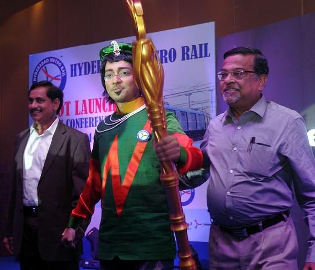A youth poses as the Mascot of Hyderabad Metro Rail that was unveiled in Hyderabad on Thursday . At left are N V S Reddy , Managing Director of HMR , and V B Gadgil ,Chief Executive & Managing Director of L&T Metro Rail (Hyderabad) Ltd. Photo: P V Sivakumar