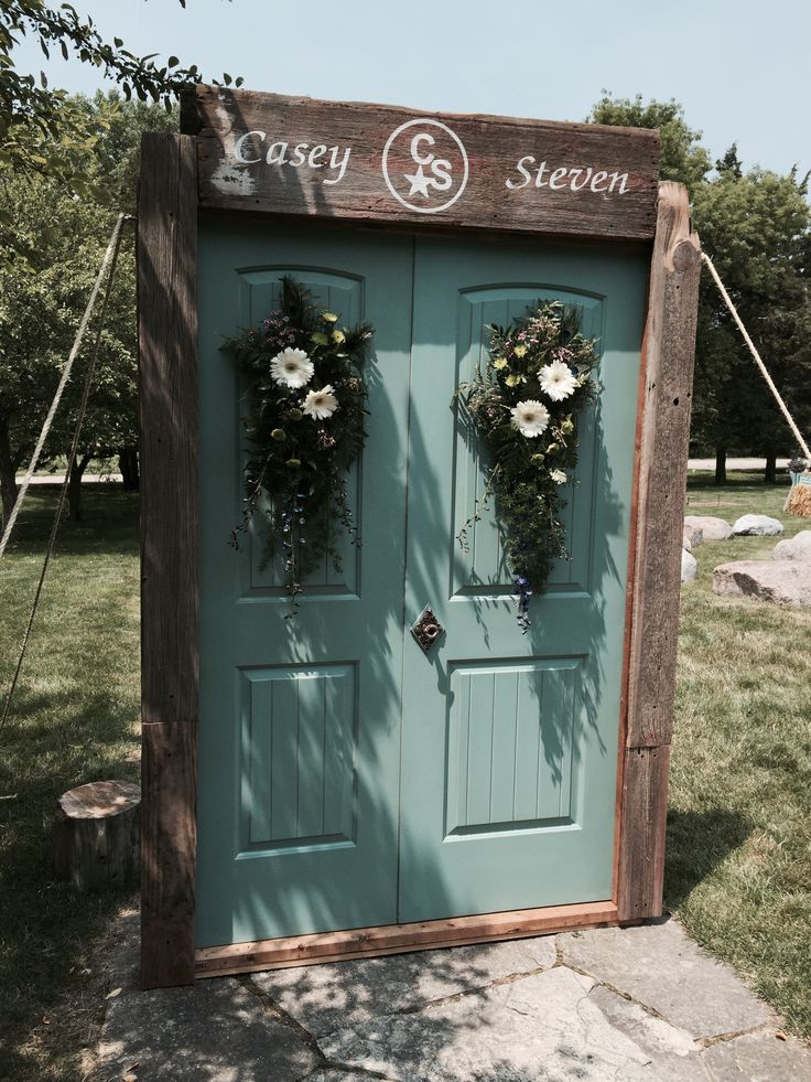 """I made this door frame for my niece's outdoor wedding. (yes, every bride needs a grand entrance!) The doors were a discount bargain find, and some of the barn wood from our grandparents' 8-sided barn that blew down. The """"logo"""" on the topper was a replica of the iron brand that the couple burned into wood in place of a unity candle, so we used that logo throughout the wedding and reception."""