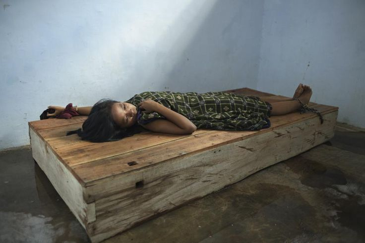 A 24-year-old female resident lies with her wrist and ankle chained to a platform bed at Bina Lestari healing center in Brebes, Central Java. After her husband abandoned her and her 5 year-old daughter to marry someone else, she began to experience depres