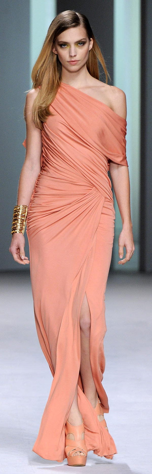 This gown is truly beautiful. This is accomplished without sequins and bling. Firstly the color is terrific, being a coral. Secondly the look seems to have just a bit of a toga feel. the unprinted material is wrapped around and around, a couple of times. Also, this has giving the gown a one open shoulder, but with that open shoulder, it has a sleeve. Remarkable and Beautiful !!!