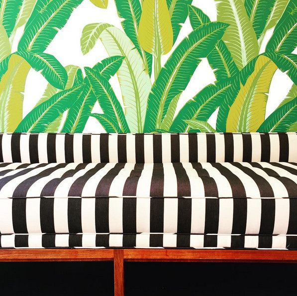 A beach house-inspired office radiates tropical vibes thanks to cabana stripes and a vibrant palm motif.