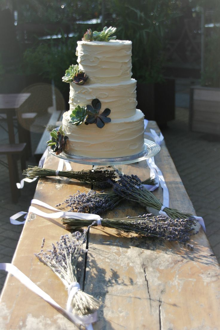 White wedding cake with real flowers and lavender. Witte bruiloft taart met echte bloemen en decoratie van lavendel op de tafel.