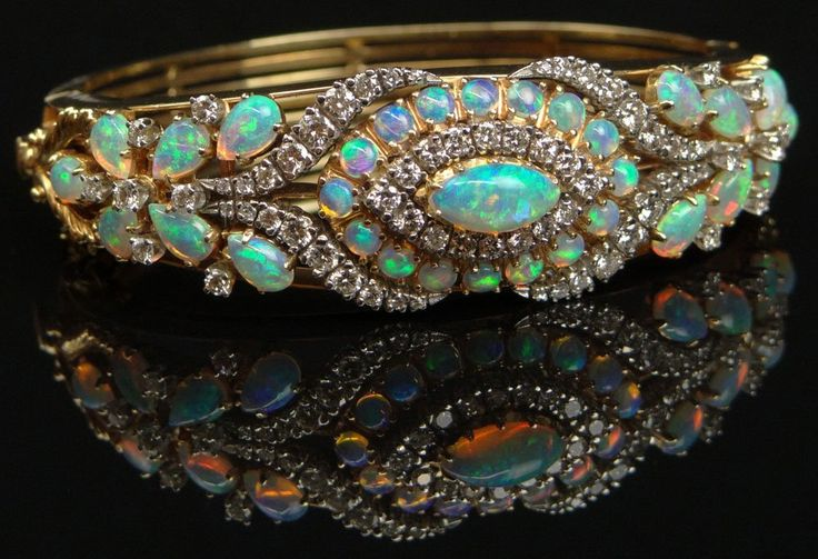 Mid Century hand made opal, 3.5 to 4.0 carats diamond, 14K yellow gold & platinum bangle bracelet | Set with 30 white opals & accented with round brilliant cut diamonds.
