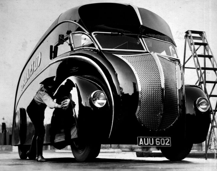 "A driver polishes his new streamlined lorry upon its arrival at Wembley, London. The lorry is mounted on a ""Commer"" two-ton chassis. Photo by Fox Photos/Getty Images. 1933"