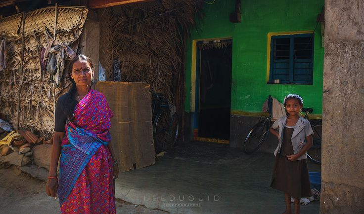 Mother and daughter stand outside of home in rural village on the outskirts of Mysuru, India.