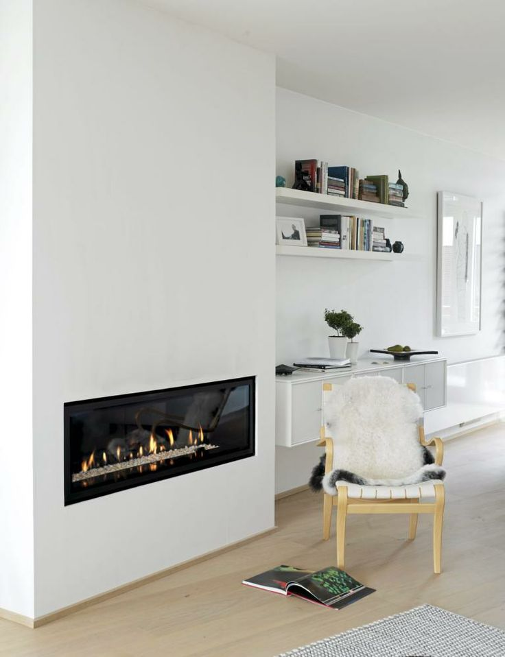 En lekker, svart peis er innfelt i den hvite veggen. Kontrastfylt og koselig.