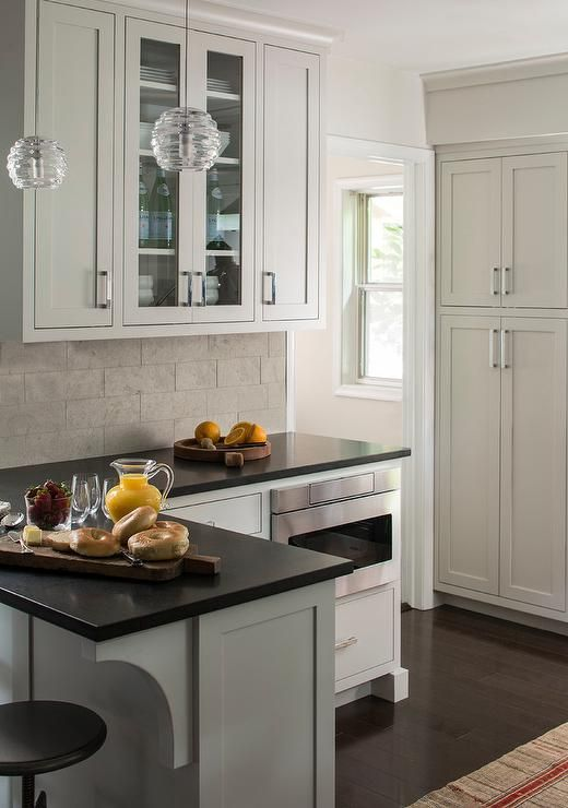 Chic kitchen features extra light gray cabinets paired with black quartz countertops and a linear gray tile backsplash.