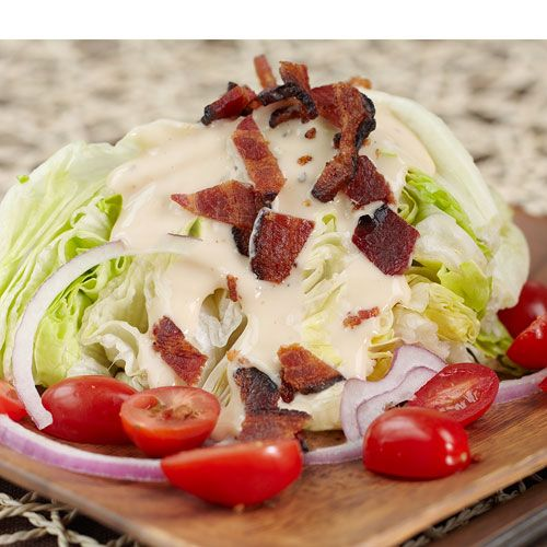 Steak House Salad ~ 1 head of Iceberg lettuce 1 cup grape tomatoes, quartered, 4 tablespoons red onion, slivered, 4 pieces cooked bacon, coarsely chopped, Stonewall Kitchen Ranch Dressing as desired, 1/4 cup crumbled blue cheese