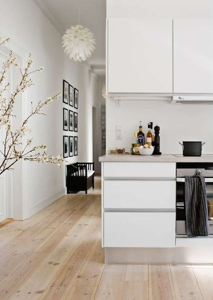 white handless kitchen units and stainless steel. Nice wooden floors, white walls and black-framed pictures in hallway. Very simple and neat.