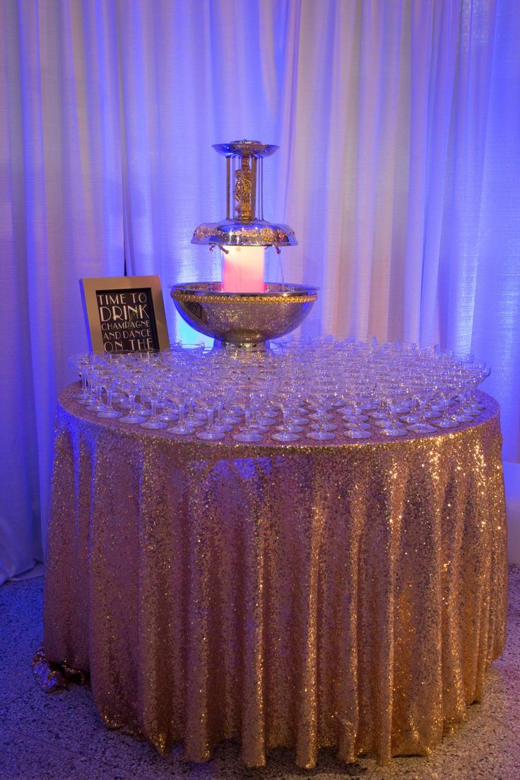 5 Gallon Champagne Fountain with champagne saucers and gold sequin table linen. Available at Weinhardt Party Rentals. St. Louis, MO Wedding.