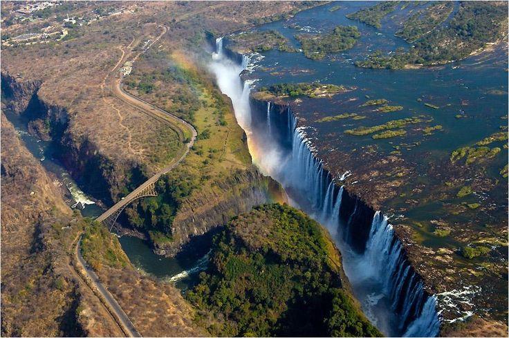 Las cataratas Victoria: Allí donde la Tierra se abre | Las cataratas Victoria en la frontera entre Zimbabue y Zambia son maravillosas. Como todo gran salto de agua, su vista desde el aire es imponente. En la fotografía también se puede apreciar el famoso puente de las cataratas, un antiguo arco de acero construido en 1905.