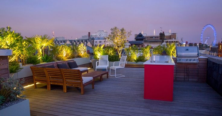 Nice Rooftop Garden With Wooden Long Padded Bench And Outdoor Kitchen Island In The Wooden Patio.