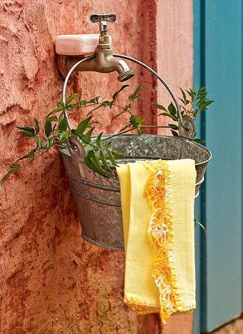 Quem disse que na roça o lavabo não precisa ter charme? Uma graça de pia improvisada com balde (furado embaixo para escoar a água) foi pendurada na torneira externa da casa de campo da jornalista Lucia Sauerbronn. #folhas #outdoor