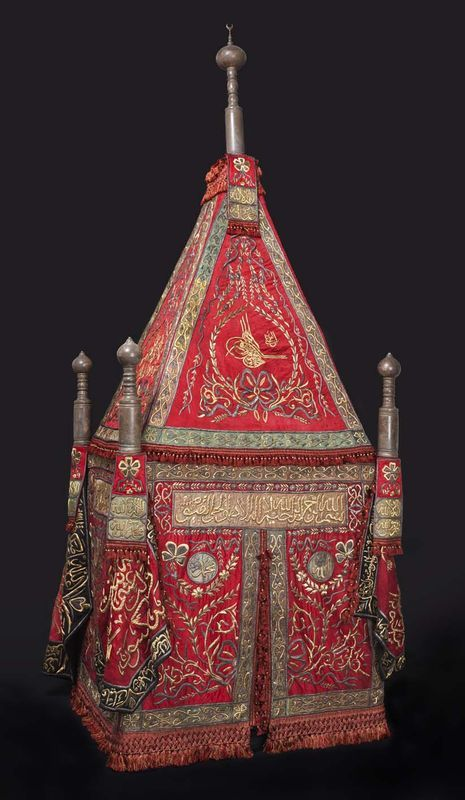 Sitr / sitarah (curtain) for the mahmal, bearing the tughra of Sultan Abdülaziz, presented by Isma'il Pasha, the khedive of Egypt, Ottoman Egypt, Cairo, 1867-76; embroidered in silver and silver-gilt wire over cotton and silk thread padding. The Mah'mal, or litter, is a wooden erection in pyramidal form and is hung by beautiful embroidered fabrics. These hangings, or coverings, accompany the litter and are intended for the most sacred sanctuary of the interior of the Mosque of Huseyn at…