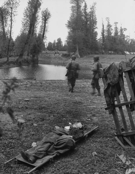 On the second day of the Normandy invasion, a wounded German sniper was found lying on a stretcher while American troops advanced into Ste. Mere-Eglise, France.