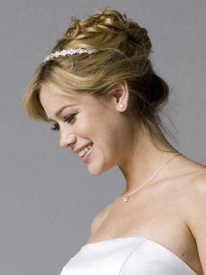 Pour le jour de son mariage, cette jeune femme a opté pour un chignon plus ou moins structuré, placé sur le haut de sa tête. Un petit diadèm...