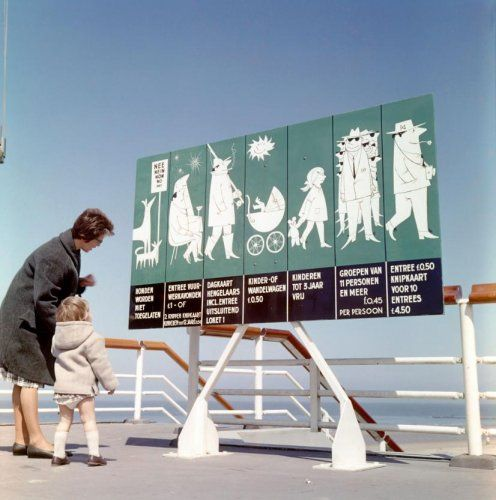 Badplaatsen. Moeder en kind voor een bord op de boulevard, voor de entree van de pier, met grappige tekeningen voor mogelijke activiteiten en daarbij behorende prijzen. Nederland, Scheveningen, 1962