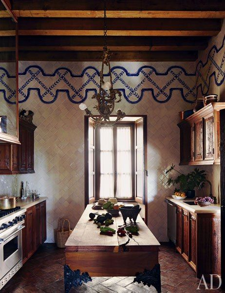A rustic kitchen in San Miguel de Allende, Mexico, features a mesquite-and-sabino-wood island with sculpted bronze legs.