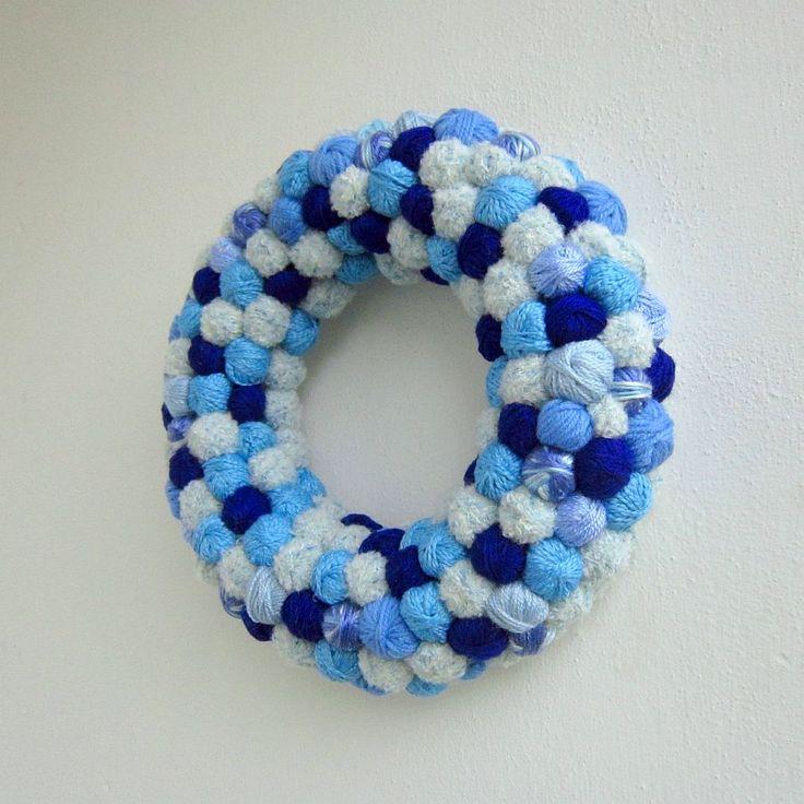 Klubíčkový věneček sv. modrý Klubíčkový věneček, vyrobený na celoroční dekoraci dveří nebo místnosti. Určitě se bude vyjímat také jako dekorace v obchodě pro tvořivé ruce nebo v galanterii. Materiál: polystyrenový korpus, akrylová příze, stuha Rozměr: průměr věnečku 31 cm Váha: 525 gr.