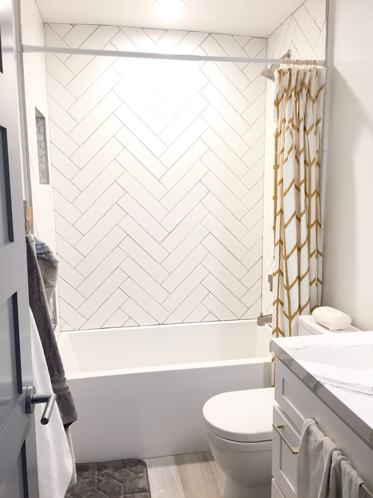 Guest shower Herringbone white subway tile gray grout