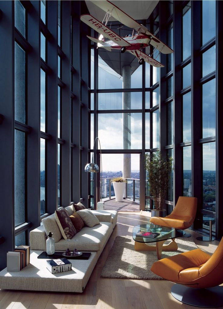 I love how they made the most of such a narrow and tall space. The hanging plane model is a nice touch and adds to the theme of being high in the air with the floor-to-roof windows and outside balcony where you can look out into the city from a grand height.
