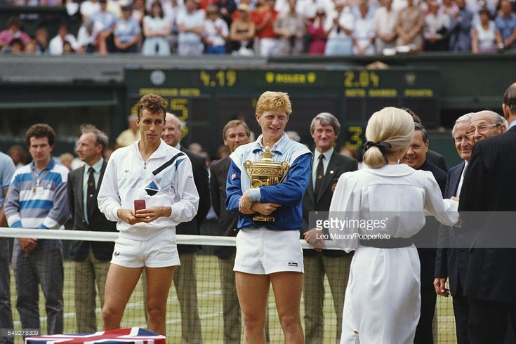 German tennis player Boris Becker holds the Gentlemen's Singles Trophy after defeating Ivan Lendl 6-4, 6-3, 7-5 in the final of the Men's Singles tournament to become champion at the Wimbledon Lawn Tennis Championships at the All England Lawn Tennis Club in Wimbledon, London on 6th July 1986. Ivan Lendl stands to the left holding his runner's up medal.
