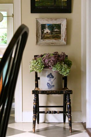Flowers in a crock sitting on the seat of a chair under picture on a small wall