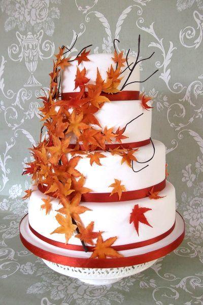 Un tort de nunta alb, cu frunze in nuante ruginii, potrivit pentru o nunta de toamna.