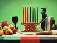 Symblos of Kwanzaa: MKEKA- straw mat foundation on which all else rest. KINARA- sevevn space candel holder, represents parents & ancestors.   MUHINDI- ears of corn represent the offspring of the parents.   ZAWADI- gifts, represents the fruit of labor, from the parents, and the rewards of seeds sown by the children. KIKOMBE CHA UMOJA- unity cup  MISHUMAA SABA-7 candels, 7 principals.Black candel in the middle represents, the People.To the right green represent the motherland, to the left red…